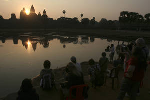 Photo - In this March 30, 2008 photo, tourists watch the sunrise at the famed Angkor Wat temple in Siem Reap province, Cambodia. Cambodia has joined hands with Australia in an effort to use the Internet to help preserve its fabled Angkor Wat temple complex. The Australian Embassy announced Thursday, July 4, 2013, that a recently-opened website, angkorsunsets.com, will allow tourists to generate recommendations for where in the 160-square-mile (400-square-kilometer) complex one can watch spectacular sunsets.  (AP Photo/Heng Sinith)