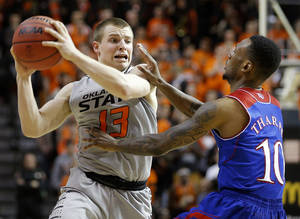 Photo - Oklahoma State's Phil Forte (13) tries to get past Kansas' Naadir Tharpe (10) during an NCAA college basketball game between Oklahoma State University (OSU) and the University of Kansas at Gallagher-Iba Arena in Stillwater, Okla., Saturday, March 1, 2014. Oklahoma State won 72-65. Photo by Bryan Terry, The Oklahoman