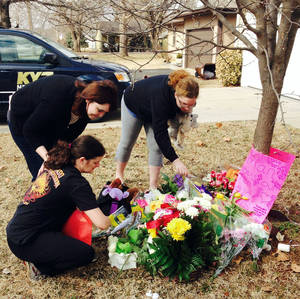 Photo - CORRECTS LAST NAME OF VICTIM'S MOTHER TO BARFIELD INSTEAD OF OWENS - Stacey Barfield, mother of Hailey Owens, kneeling, and family members Sara Wells, left, and Teri Nord arrange flowers left by well wishers Thursday, Feb. 20, 2014 near the site where the 10-year-old girl was abducted just blocks from the Springfield, Mo., home. Prosecutors have charged Craig Michael Wood with first-degree murder, kidnapping and armed criminal action in their girls death. Prosecutors says the fourth-grader's body was found stuffed in two trash bags inside plastic storage containers in the basement of Wood's Springfield home. She had been shot in the head. (AP Photo/Alan Scher Zagier)
