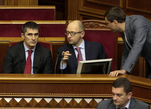 Photo - Ukrainian Prime Minister Arseniy Yatsenyuk, center,  and  new Ukrainian prosecutor-general Vitaly Yarema, left,   during a session of the parliament in Kiev, Ukraine, Thursday, June 19, 2014. The Ukrainian parliament on Thursday approved Ukraine's new foreign minister, prosecutor-general and National Bank Chief.  (AP Photo/Sergei Chuzavkov)
