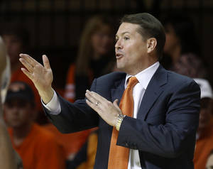Photo - Oklahoma State coach Travis Ford gestures to his team in the first half of an NCAA college basketball game against Mississippi Valley State in Stillwater, Okla., Friday, Nov. 8, 2013. Oklahoma State won 117-62. (AP Photo/Sue Ogrocki)