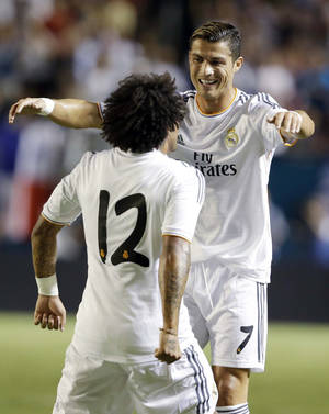 Photo - Real Madrid forward Cristiano Ronaldo (7) congratulates defender Marcelo Vieira (12) after Vieira scored a goal during the first half of the International Champions Cup final soccer game against Chelsea, Wednesday, Aug. 7, 2013, in Miami Gardens, Fla. (AP Photo/Wilfredo Lee)