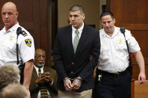 Photo - Former New England Patriots tight end Aaron Hernandez is led into the courtroom to be arraigned on homicide charges at Suffolk Superior Court in Boston, Wednesday, May 28, 2014. Hernandez pleaded not guilty in the shooting deaths of Daniel de Abreu and Safiro Furtado. He already faces charges in the 2013 killing of semi-pro football player Odin Lloyd. (AP Photo/Dominick Reuter, Pool)