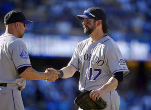 Photo - Colorado Rockies manager Walt Weiss, left, shakes hands with Todd Helton after the Rockies defeated the Los Angeles Dodgers 2-1 in a baseball game, Sunday, Sept. 29, 2013, in Los Angeles. Helton was playing in the final game of his career. (AP Photo/Mark J. Terrill)