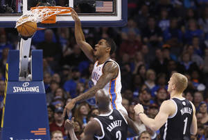 Photo - Oklahoma City Thunder forward Perry Jones (3) dunks in front of Brooklyn Nets center Kevin Garnett and forward Mason Plumlee (1) in the second quarter of an NBA basketball game in Oklahoma City, Thursday, Jan. 2, 2014. (AP Photo/Sue Ogrocki)