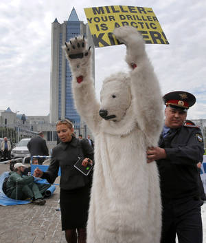 Photo -   A police officer detains s Greenpeace activist dressed as a polar bear outside Gazprom's headquarters in Moscow, Russia, Wednesday, Sept. 5, 2012. Russian and international environmentalists are protesting against Gazprom's plans to pioneer oil drilling in the Arctic. (AP Photo/Misha Japaridze)