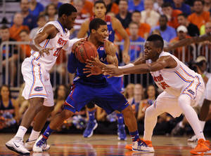 Photo - Univ. of Kansas guard Frank Mason (0) tries to keep the ball with Florida guard Michael Frazier II (20) and Florida forward Will Yeguete (15) try to get possession during the first half of an NCAA college basketball game Tuesday, Dec. 10, 2013 in Gainesville, Fla.  (AP Photo/Phil Sandlin)