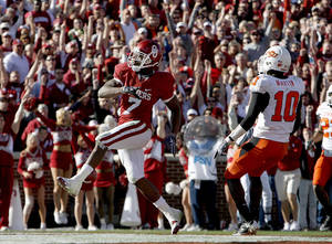 Photo -  OU's DeMarco Murray (7) scores a touchdown in front of OSU's Martin Markelle (10) during the second half of the Bedlam college football game between the University of Oklahoma Sooners (OU) and the Oklahoma State University Cowboys (OSU) at the Gaylord Family-Oklahoma Memorial Stadium on Saturday, Nov. 28, 2009, in Norman, Okla. Photo by Sarah Phipps, The Oklahoman