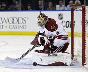 Photo - Phoenix Coyotes goalie Mike Smith makes a save during the second period of the NHL hockey game against the New York Rangers, Monday, March 24, 2014, in New York. (AP Photo/Seth Wenig)
