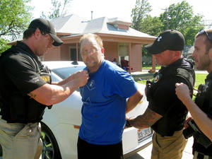 Photo - Bounty hunters Ryan Lopez, Mike Parsons and Eric London apprehend Wesley Baker, 36, who missed a court date in Oklahoma County and had several outstanding warrants. <strong>Matt Dinger</strong>