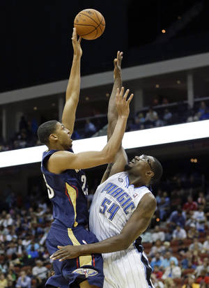 Photo - New Orleans Pelicans' Anthony Davis, left, shoots over Orlando Magic's Jason Maxiell (54) during the first half of an NBA preseason basketball game in Jacksonville, Fla., Wednesday, Oct. 9, 2013. (AP Photo/John Raoux)