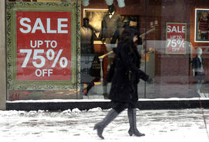 Photo - In this Jan 2, 2014 photo, a pedestrian passes by sale signs on a store front window in Chicago. The Conference Board releases the Consumer Confidence Index for January, on Tuesday, Jan. 28, 2014. (AP Photo/Kiichiro Sato)