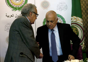 photo - U.N.-Arab League envoy to Syria Lakhdar Brahimi, left, shakes hands with Arab League Secretary-General Nabil Elaraby following a joint press conference at the Arab League headquarters in Cairo, Egypt, Sunday, Dec. 30, 2012. The international envoy to Syria warned Sunday that as many as 100,000 could die in the next year if a solution is not reached quickly to end the country's civil war. (AP Photo/Nasser Nasser)