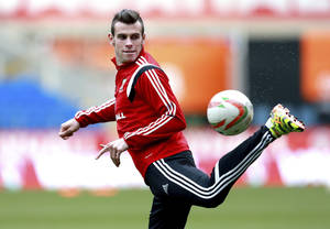 Photo - Wales' Gareth Bale during a training session with other members of the Wales soccer team at The Cardiff City Stadium, Cardiff, Wales, Tuesday March 4, 2014. Wales will play Iceland in a friendly soccer match Wednesday. (AP Photo/David Davies, PA) UNITED KINGDOM OUT - NO SALES - NO ARCHIVES