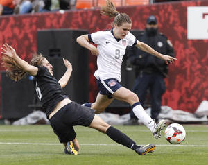 Photo - US Women's National Team's Heather O'Reilly (9) leaps over New Zealand Women's National Team's Rebekah Stott in the second half of an international friendly soccer match on Sunday, Oct. 27, 2013, in San Francisco. US won 4-1. (AP Photo/Tony Avelar)