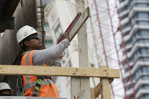 Photo -  A construction worker works on the site of the SoMa at Brickell apartment building in downtown Miami.   AP File Photo  <strong>Lynne Sladky -  AP </strong>
