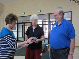 Photo - Volunteer Saundra Cruse, wife of Ron Cruse, distributes prayers to Blood Pressure Prayer Clinic participants Margaret and Dale Barnes of Edmond. <strong>Carla Hinton - The Oklahoman</strong>