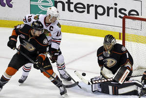 Photo - Chicago Blackhawks center Jonathan Toews (19) attacks as Anaheim Ducks goalie Jonas Hiller (1), of Switzerland, and defenseman Luca Sbisa (5), of Italy, defend during the second period of an NHL hockey game in Anaheim, Calif., Wednesday, Feb. 5, 2014. (AP Photo/Reed Saxon)