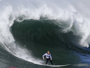 Photo - Ryan Augenstein competes during the third heat of the Mavericks Surf Competition in Half Moon Bay, Calif., Sunday, Jan. 20, 2013. (AP Photo/Marcio Jose Sanchez)