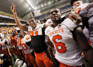 photo - OSU's Justin Blackmon (81), left, and Andrew McGee (6) sing the alma mater with the rest of the team after the Valero Alamo Bowl college football game between the Oklahoma State University Cowboys (OSU) and the University of Arizona Wildcats at the Alamodome in San Antonio, Texas, Wednesday, December 29, 2010. OSU won, 36-10. Photo by Nate Billings, The Oklahoman ORG XMIT: KOD