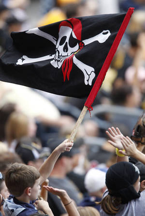 "Photo - FILE - In this Sept. 9, 2012, file photo, a young Pittsburgh Pirates fan waves a Jolly Roger flag during the Pirates' baseball game against the Chicago Cubs in Pittsburgh. The Pirates announced on Wednesday, Jan. 8, 2014, the franchise will make the gold ""P"" the team's primary logo this season, replacing the beloved eye-patch wearing sailor who has been the club's main symbol for nearly 80 years. (AP Photo/Keith Srakocic, File)"