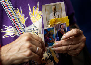 photo - A woman holds a trio of images showing Venezuelan St. Jose Gregorio Hernandez, top, renowned as the ``Doctor of the Poor''; a laminated holy card of Jesus Christ; and an image of Venezuela's President Hugo Chavez, right, at a church service where supporters of the ailing president gathered to pray for his health, in Caracas,Venezuela, Thursday, Dec. 13, 2012.  Venezuelans were warned that Chavez may not be well enough after his fourth cancer-related surgery in Cuba to be inaugurated on Jan. 10.  (AP Photo/Fernando Llano)