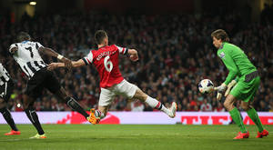 Photo - Arsenal's Laurent Koscielny, kicks the ball past Newcastle's goalkeeper Tim Krul to score the opening goal during, their English Premier League soccer match between Arsenal and Newcastle United at the Emirates stadium in London, Monday, April 28,  2014. (AP Photo/Alastair Grant)