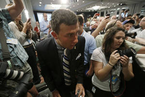 Photo - Texas A&M quarterback Johnny Manziel fights his way through a crowd of photographers and reporters as he arrives for the Southeastern Conference football Media Days in Hoover, Ala., Wednesday, July 17, 2013. (AP Photo/Dave Martin)