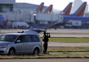 Photo - A member of the security detail keeps watch on the tarmac while awaiting the arrival of President Barack Obama at Love Field Airport, Wednesday, Nov. 6, 2013, in Dallas. (AP Photo/Tony Gutierrez)