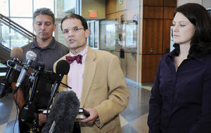 photo -   Defense attorney Jim Fleming, center, is flanked by Todd Hoffner, left, and his wife Melodee Hoffner as he makes a statement, Wednesday, Oct. 31, 2012, following Todd Hoffner's court testimony in Mankato, Minn., on child pornography charges. Hoffner, the suspended head football coach at Minnesota State, Mankato who is accused of making pornographic videos of his children, told a judge Wednesday that the images merely show a skit that his children came up while in the bathtub and asked him to record. (AP Photo/The Mankato Free Press, John Cross)