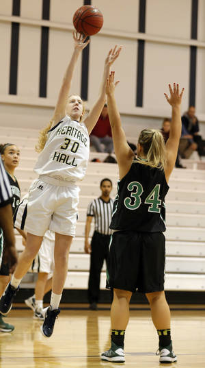 Photo - Heritage Hall's Rachel Moore shoots over McGuinness' Allison Frey during a girls high school basketball game between Heritage Hall and Bishop McGuinness at the Heritage Hall basketball tournament Oklahoma City.,  Friday,Dec. 28, 2012. Photo by Sarah Phipps, The Oklahoman