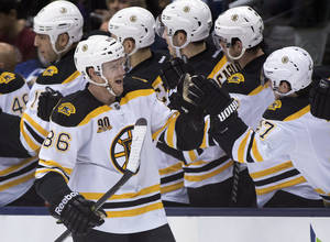 Photo - Boston Bruins defenceman Kevan Miller (86) is congratulated by teammates after scoring on the Toronto Maple Leafs during the second period of an NHL hockey game in Toronto on Sunday, Dec. 8, 2013. (AP Photo/The Canadian Press, Frank Gunn)