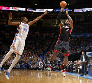Photo - Heat forward LeBron James shoots a 3-pointer over Thunder forward Kevin Durant during Thursday night's matchup. James finished with a game-high 33 points, while Durant led OKC with 28.  Photo by Bryan Terry,  The Oklahoman
