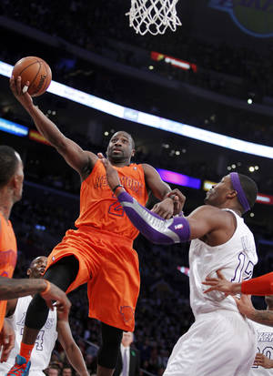 photo - New York Knicks guard Raymond Felton (2) shoots against Los Angeles Lakers center Dwight Howard, right, during the second half of their NBA basketball game in Los Angeles, Tuesday, Dec. 25, 2012. The Lakers won 100-94. (AP Photo/Alex Gallardo)