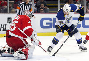 Photo - Detroit Red Wings goalie Jimmy Howard (35) stops a St. Louis Blues wing T.J. Oshie (74) shot in the first period of an NHL hockey game, Monday, Jan. 20, 2014, in Detroit. (AP Photo/Paul Sancya)