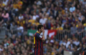Photo - Barcelona's Lionel Messi from Argentina puts his hand on his mouth during a Spanish La Liga soccer match between FC Barcelona and Atletico Madrid at the Camp Nou stadium in Barcelona, Spain, Saturday, May 17, 2014. (AP Photo/Andres Kudacki)