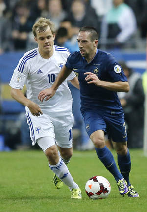 Photo - France's Franck Ribery, right, dribbles Teemu Pukki of Finland during their 2014 World Cup Group I qualifying soccer match  at the Stade de France stadium in Saint Denis, north of Paris, France, Tuesday, Oct. 15, 2013. (AP Photo/Francois Mori)