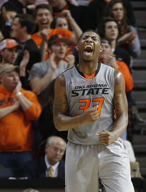 Photo - Oklahoma State's Markel Brown (22) celebrates during an NCAA college basketball game between Oklahoma State University (OSU) and the University of Kansas at Gallagher-Iba Arena in Stillwater, Okla., Saturday, March 1, 2014. Oklahoma State won 72-65. Photo by Bryan Terry, The Oklahoman