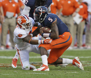 Photo - Virginia quarterback David Watford (5) is sacked by Clemson cornerback Darius Robinson (8) during the first half of an NCAA college football game in Charlottesville, Va., Saturday, Nov. 2, 2013. Clemson won the game 59-10.   (AP Photo/Steve Helber)