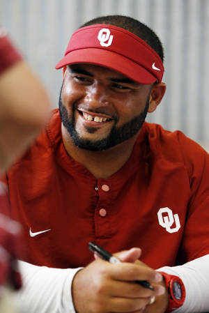 Photo - COLLEGE FOOTBALL: Jerry Montgomery, defensive line coach, signs autographs during fan appreciation day for the University of Oklahoma Sooner (OU) football team at Gaylord Family-Oklahoma Memorial Stadium in Norman, Okla., on Saturday, Aug. 3, 2013. Photo by Steve Sisney, The Oklahoman