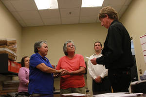Photo - Catherine Martinez and Linda Montoya hold hands as Dona Ana County employee and reverend Jess C. Williams marries them at the Dona Ana County Clerk's Office in Las Cruces, New Mexico, Wednesday, Aug. 21, 2013. More than 40 same-sex couples obtained their marriage licenses after the county clerk announced the county would be the first in New Mexico to marry same-sex couples. (AP Photo/Juan Carlos Llorca)