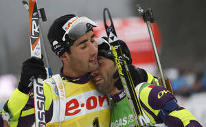 Photo - FILE - In this March 11, 2012 file photo, Martin Fourcade of France, left, hugs his brother Simon Fourcade after winning the men's mass start 15K race at the Biathlon World Championships in Ruhpolding, Germany. When Martin Fourcade won his first Olympic gold on Feb. 13, 2014, one of the best feelings for the French biathlete was celebrating in the finish area with the teammate he grew up trying to beat _ older brother Simon. All over Sochi, siblings are competing next to each other _ some as teammates, some as rivals for the gold medal. (AP Photo/Matthias Schrader, File)
