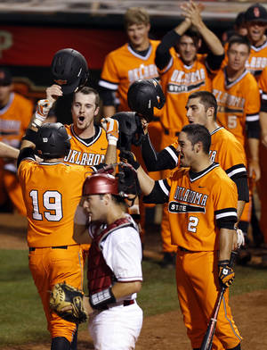 Photo - The OSU Cowboys celebrate a 3-run home run by Aaron Cornell (19) in the eighth inning near OU catcher Anthony Hermelyn (9) during a Bedlam college baseball game between Oklahoma and Oklahoma State in the Big 12 baseball tournament at the Chickasaw Bricktown Ballpark in Oklahoma City, Friday, May 23, 2014. Photo by Nate Billings, The Oklahoman