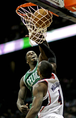 Photo - Boston Celtics' Brandon Bass, left, dunks the ball over Atlanta Hawks' Paul Millsap during the fourth quarter of an NBA basketball game, Saturday, Nov. 23, 2013, in Atlanta. Boston won 94-87. (AP Photo/David Goldman)