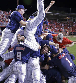 Photo - Mississippi celebrates their victory over Louisiana Lafayette during an NCAA college baseball tournament super regional game in Lafayette, La.,Monday, June 9, 2014. Mississippi won 10-4 to advance to the College World Series. (AP Photo/Gerald Herbert)