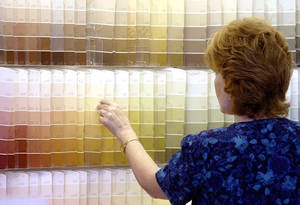 Photo -   FILE -In this Monday June 28, 2004, file photo, a customer looks over color chips at a Sherwin Williams store in Columbus, Ohio. Sherwin-Williams is buying the privately held Mexican paint company Consorcio Comex in an all-cash deal valued at about $2.34 billion. Consorcio Comex, S.A. de C.V., sells paints and coatings under several brands in the United States and Canada, and it sells architectural and industrial coatings in Mexico. It has company-operated stores and also works with independent paint dealers. The company is based in Mexico City and (AP Photo/Jay LaPrete, File)