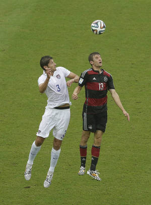 Photo - United States' Omar Gonzalez and Germany's Thomas Mueller (13) go up for a ball during the group G World Cup soccer match between the USA and Germany at the Arena Pernambuco in Recife, Brazil, Thursday, June 26, 2014. (AP Photo/Hassan Ammar)