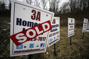 Photo - FILE - In this Monday, Jan. 13, 2014, file photo, a  sold sign is placed on a homesite in the Grace Manor townhouse development in Robinson Township, Pa. Freddie Mac, the mortgage company, releases weekly mortgage rates, on Thursday, April 3, 2014. (AP Photo/Gene J. Puskar, File)