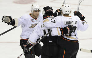 Photo - Anaheim Ducks center Andrew Cogliano, left, celebrates with Saku Koivu (11), of Finland, and Hampus Lindholm (47), of Sweden, after Lindholm scored a goal in the third period of an NHL hockey game against the Nashville Predators on Saturday, Feb. 8, 2014, in Nashville, Tenn. The Ducks won 5-2. (AP Photo/Mark Zaleski)
