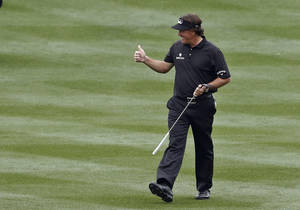 Photo - Phil Mickelson gives a thumbs-up to the cheering crowd as he walks up the 18th fairway during the final round of the Waste Management Phoenix Open golf tournament on Sunday, Feb. 3, 2013, in Scottsdale, Ariz. (AP Photo/Ross D. Franklin)